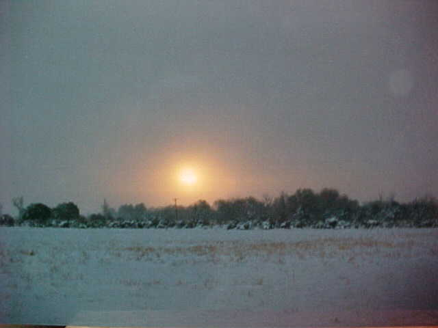 Misty winter sunset with the sun visible in the clouds and snow over the open field.